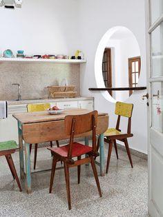 La cocina de esta casa remodelada es en L y rodea al comedor diario. Tiene una mesa extensible y un pasaplatos circular cruzado por una baranda.