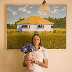 Reg Mombassa with a version of his 1974 painting House at Beach Road with Kirk's Bush, which hangs on his kitchen wall.