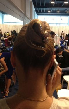 Simple high bun with a single swirl accented by rhinestones. Good hairstyle for latin and standard ballroom. Visit http://ballroomguide.com/comp/hair_make_up.html for more hair and makeup info