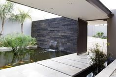 contemporary-residential-architects-with-Water-feature-over-the-stone-walls-at-the-fish-pond-beside-concrete-stepping-stone-on-the-entrance-...