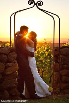 A sunset wedding day kiss at the vineyard at Domaine Margelle -- Presented by Portland Wedding Venues