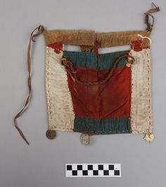 Face veil Size (cm):21 x 20 Saudi Arabia, Asir Date of object:Late 20th century Material(s):Cotton, leather, metal, shell Techniques:Factory woven cotton cloth, hand made metal beads, factory made imitation coins, leather strips  Face veil made from brick red cotton cloth decorated with small metal beads, imitation coins, and a shell button. The reverse side is lined with cotton cloth in white, blue, red and orange. The veil is tied using leather strips.