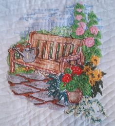 "This beautiful garden scene art quilt features a garden bench nested nestled in the flowers.  The size of the art quilt is approximately 12"" W x 12"""