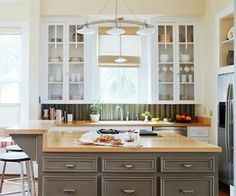 Have you ever thought about using corrugated metal for a backsplash? It combines nicely with the classic wood cabinets in this upscale kitchen.