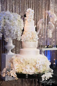 Featured Photographer: Andre LaCour Photography, Via Yanni Design Studio; Glamorous sky high white wedding cake covered in orchids