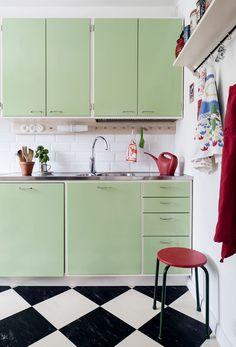 Oraksen hana on ainoa asia, joka vanhasta keittiöstä säästettiin. Pehmeän vihreät kaapit ovat pellavaöljymaalattua koivua, vetimet ovat helsinkiläisestä Hokola-helakaupasta. Tiskiallastaso on Franken. Vanha jakkara ja kastelukannu ovat Anninan mummin vanhoja. Renowan sieviä katkaisijoita ja pistorasioita myydään rautakaupoissa. Linoleumilattia on Forbon. 1950s Kitchen, Vintage Kitchen, Kitchen Dining, Kitchen Cabinets, 60s Furniture, House Rooms, Country Kitchen, Home Decor Inspiration, Cool Kitchens