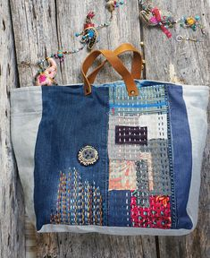 Maxi Japanese inspiration bag from fenomen brand. For this large bag, I used different pieces of denim and gray linen. The front is composed of embroideries that I made by hand with an assortment of patchwork of fabrics. For this model, I was inspired by Japanese art, the boro