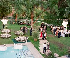 Inflatable swans floating in the pool and trees wrapped in strands of lights gave this classy affair a touch of whimsy to a backyard wedding.