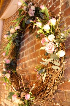 Spring flower adorned wall wreath, lovely backdrop for the alter.