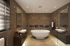 Einheitlich glänzende braunen Mauern umgeben einer Eitelkeit-Theke und eine freistehende ovale Badewanne in der Mitte des Raumes.
