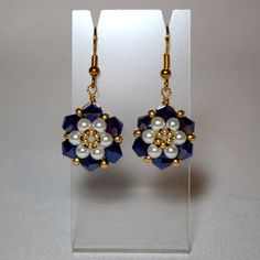 Sapphire AB crystals and icy white glass pearls are stitched forming beautiful rosettes embellished with gold seed beads. Suspended from gold by anita Full Bloom Right Angle Weave Earrings -- NOTICE how a wire is run through the top bicone and a wire wrap Bead Jewellery, Seed Bead Jewelry, Beaded Jewelry, Jewelery, Handmade Jewelry, Seed Bead Earrings, Beaded Earrings, Seed Beads, Woven Bracelets