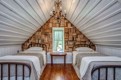 The upstairs loft of this Tennessee cabin sleeps two, with matching twin beds. Its wall of stacked books gives the room a dramatic focal point.