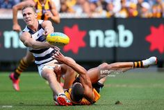 Joel Selwood of the Cats handballs whilst being tackled by Josh Gibson of the Hawks during the round one AFL match between the Hawthorn Hawks and the Geelong Cats at Melbourne Cricket Ground on April 6, 2015 in Melbourne, Australia.