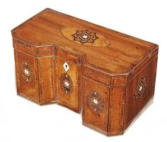 A 19th century mahogany tea caddy, with an inverted breakfront and inlaid stringing and parquetry star panels in specimen woods and bone, the interior with three lidded compartments, 5in (13cm) h, 9.25in (23.5cm) w, 5in (13cm) d. Woolley & Wallis