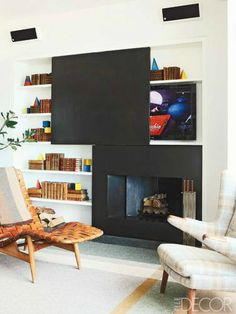 8 Unique Fireplaces from Around the World - Hidden TV Above Fireplace - In a Manhattan loft library, the fireplace surround and sliding panel are of blackened metal, and the television is by Samsung.