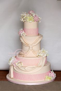 Four tiered wedding cake with pastel pink roses and detailing; beige draping ribbon; green detailing, flowers