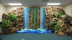 """finished falls w/more """"rocky"""" walls and greenery. Storage & file cabinets of classroom become foundation for rock walls & cliffs on both sides of falls Jungle Decorations, School Decorations, Vbs Crafts, Diy And Crafts, Waterfall Decoration, Deco Jungle, Jungle Safari, Vbs Themes, Classroom Themes"""