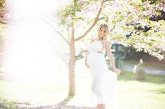 Blond Beach waves, White maternity gown. Delicate flower crown under the cherry blossom tree.
