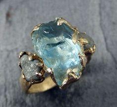 Raw Uncut acquamarina diamante oro anello di fidanzamento anello di nozze Custom uno di un gentile gemma anello su misura tre pietra anello byAngeline acquamarina grezza grezzo, circondato da due diamanti grezzi gratis. Scolpito questo anello in cera a mano ed eseguirne il cast in tinta oro 14k utilizzando il processo di fusione a cera persa. Questo di un anello di pietra preziosa crudo gentile è una dimensione di 5 1/2. Acquamarina pietra misura circa 13 X 8 mm. I diamanti grezzi sono c...