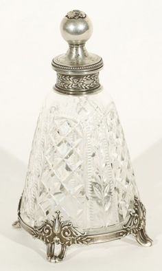 A CUT GLASS AND SILVER PERFUME BOTTLE, BOLIN, MOSCOW, 1899-1908, the tapered cylindrical body with cut glass panels of floral and geometric ornament, silver mounted on four feet, the stopper with a ball-shaped finial, height: 12.5 cm. (5 in.), marked Bolin, 88 standard