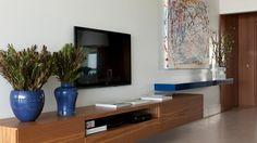 A sobreposição do aparador e da estante de TV - que ocupam toda a extensão da parede - resulta na composição de um espaço dinâmico e elegante para o living do apartamento na Riviera de São Lourenço, decorado pelo arquiteto Diego Revollo