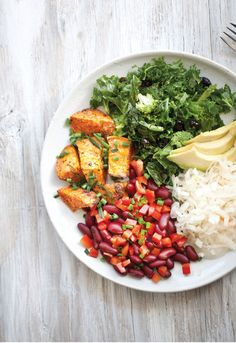 A healthy and delicious Nourish Bowl with Kale and Broccoli Salad, Sweet Potatoes, Sauerkraut and Bean Salsa.