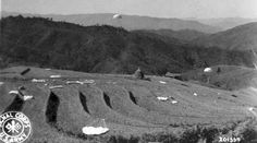 Terraced field filled with parachutes dropping supplies for WWII soldiers in Burma. Photographer Unknown