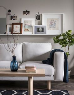 A picture ledge sits above a sofa and holds framed photos and artwork, while smaller photos are hung with decorative tape.