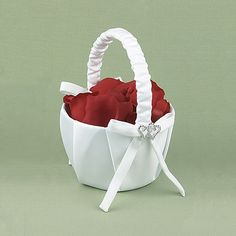 White satin flower basket with satin ribbon accents and silver-plated, rhinestone heart adornments.  Petals not included.