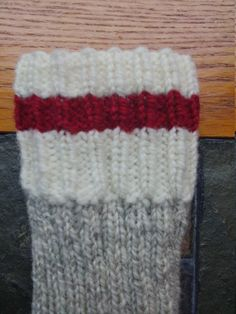 A Custom item. Please allow 2 weeks for completion. Handknit heavy Wool Socks made in the traditional way to be warm and long lasting. Natural coloured cuffs toes and heels, red stripe and grey twist body, in the sock monkey style. Heels and toes are reinforced with nylon to be long lasting. Perfect for working outside or hiking. Leg Length is 11 inches when laid flat, please specify mens or womens shoe size. Please check shop announcements for accurate turn around times. Machine wash in…