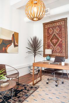 Thiswarm andwelcoming executive office harbors a unique mix of bohemian and mid century modern elements. Including patterned rugs, sculptural wood furnishings and plants keeps things feeling friendly, while airy ceilings add to the feeling of openness.