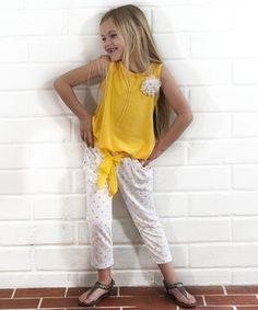 Basic without being boring, this tank gets the perfect trendy touch thanks to its tie front fit. A bright polka dotted capri completes the look, aided in ease with its slip-on elastic waistband.