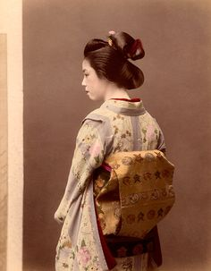 This is the picture of a woman Geisha. Late 1860's through all of 1880 was known as the Golden Age of the Geisha. In her bag, she has whatever arts she decided to pursue. Whether it be painting, dancing, or martial arts, she kept all of her needed luggage in the bag. Woman's hair was always kept up.