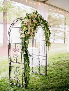 Wrought iron arch with luscious asymmetrical florals... roses, ruscus, stock, hanging amaranthus.