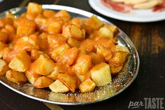 """Patatas Bravas (papas bravas) One of the most common raciones found across Spain, these """"brave potatoes,"""" come with one of several varieties of sauces, ranging from allioli to spicy pepper sauce. #SpanishCuisine #Food #Travel #SpanishFood"""