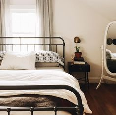 Wrought iron bed, midcentury bedside table.