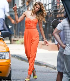 Australian beauty Jessica Hart looked stunning in a strapless orange jumpsuit paired with neon yellow and blue strappy heels and gold bangles. via dailymail.co.uk