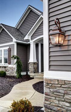 Love the colors, stone & oil bronzed light fixtures with the pops of white trim. Just love. And the black mulch is a great contrast as well.