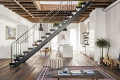Kitchen and dining areas are divided by a custom, steel and solid wood tread stair in this three-story townhouse in Williamsburg. [4200 × 2803]