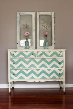 A vintage dresser makeover with aqua chevron on the drawers and staged with pink peonies and salvaged windows.
