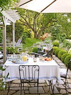 Al fresco dining is gorgeous surrounded by greenery and a pretty tablecloth. Plenty of opportunity for a shady spot with umbrella and pergola. I am ready to pull up a chair!