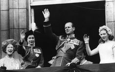 Queen Elizabeth, Prince Philip and Princess Anne wave to crowds from the balcony of Buckingham Palace in 1963