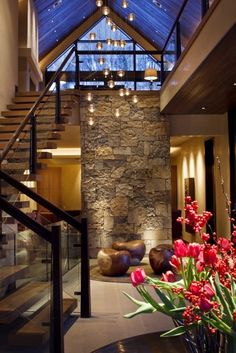 Cabin zen. Floating wood stairs, multiple pendant lights, large windows, stone fireplace