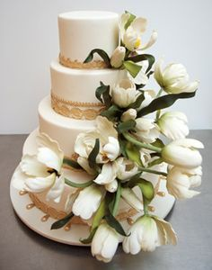 Brides.com: . This ivory fondant-covered cake is decorated with gold trim at the base of each of the four tiers and a lush cascade of sugar tulips. Cake design by Ron Ben-Israel.