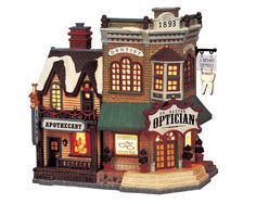 Lemax Dr. Baxter Optician, Ivan' Apothecary.  SKU# 05465 . Introduced in 2000 and retired in 2004, this porcelain Lighted building was made for the Caddington Collection.