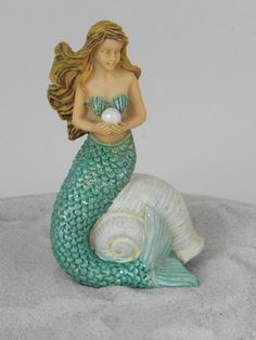 A beautiful mermaid that is resting on a shell. Shell be perfect for your beach themed fairy garden, miniature garden or terrarium. She has long flowing hair and is holding a pearl.  Made of resin. I have added a weatherproof fairy dust glitter to her tail for an added touch of sparkle and whimsy. ✿ Mermaid measure approximately 3 inches tall x 1 1/2 inches wide x 1 1/4 inches deep.  Any accessories pictured are not included and are for illustrative purposes only.  PLEASE NOTE that ... Mermaid Cove, Mermaid Fairy, Mermaid Dolls, Real Mermaids, Mermaids And Mermen, Model Magic, Garden Cakes, Mermaid Glitter, Fairy Garden Supplies