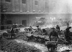 INDUSTRY DURING FIRST WORLD WAR (Q 54623)   Female workers load wheelbarrows with coke and ashes at a London gas works during the First World War.