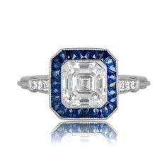 A stunningAsscher and Sapphire Halo Engagement Ring,featuring a lively 1.80ct asscher cut diamond, and set in handcrafted platinum.