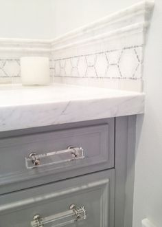 Seventy Five Arlington - bathrooms - white marble countertops, white marble counter, mosaic marble tiles, mosaic marble accent tiles, medicine cabinet, lucite pulls, lucite hardware, gray vanity, gray bathroom vanity,