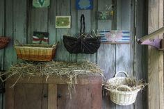 No chicken coop is complete without nesting boxes and roosting perches. Here, sturdy wicker baskets padded with straw serve as cozy places for hens to lay their eggs, while a wood closet rod acts as a perch for sleeping. Colorful paintings hung on the wall make egg collecting that much more fun.